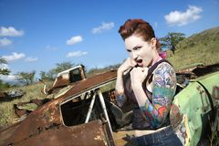 Sexy tattooed woman. Angry tattooed Caucasian woman with fists clenched ready to fight in junkyard Stock Photo