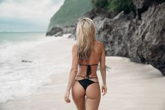 Tattooed young girl in black swimsuit posing on the beach, tunn with her back to camera. Beautiful blonde woman. With long hair relaxing at the ocean. Concept royalty free stock image