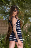 Tattooed young woman. Young woman with sunglasses and tattooed arm posing with tree in background royalty free stock photos