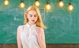 Sexy teacher concept. Woman with long hair in white blouse stands in classroom. Lady strict teacher on dreamy face. Stands in front of chalkboard. Teacher with royalty free stock image