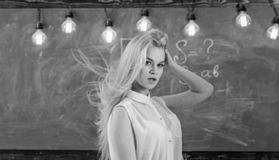 Teacher concept. Woman with long hair in white blouse stands in classroom. Teacher with waving long blonde hair. Looks sexy. Lady strict teacher on dreamy face stock image