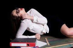 Sexy teacher posing on desk in studio on black background.  Royalty Free Stock Photo