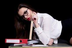 Sexy teacher posing on desk in studio on black background.  Stock Image