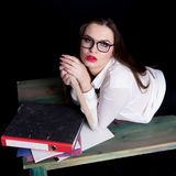 Sexy teacher posing on desk in studio on black background.  Royalty Free Stock Photography