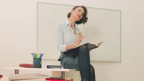 teacher with a writing board in classroom or office