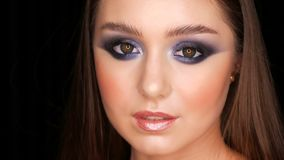 Sexy tender beautiful young model with long hair and blue evening make-up smoky eyes posing in front of the camera on stock video