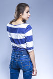 and Thin Caucasian Brunette Girl in Jeans and Striped Shirt Stock Images