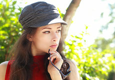 thinking young woman in cap holding sun glasses Stock Photos