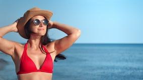 Sexy toeristenvrouw in zwempak genieten die bij blauwe overzeese achtergrond tijdens vakantie zonnebaden stock videobeelden