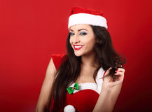Sexy toothy smiling woman in santa clause costume with bright ma. Keup and red lipstick posing on bright red background Royalty Free Stock Images