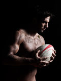 Sexy topless rugby man portrait. One caucasian sexy topless man portrait holding a rugby ball on studio black background a rugby ball on studio black background Stock Photography