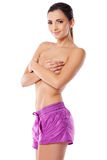 Sexy topless woman in pink shorts. Beautiful smiling sexy topless young woman with a lovely body posing sideways looking at the camera in cute pink shorts Royalty Free Stock Photos