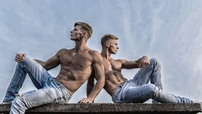 Sexy torso attractive body. Denim pants emphasize masculinity sexuality. Men twins brothers muscular guys sit relax sky