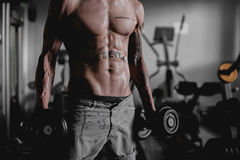 Sexy torso of wet man fall off treadmill in gym. Man in gym doing exercise with dumbbells. Muscular man torso with tatoos in gym Stock Photo
