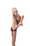 Sexy trainer demonstrates exercise with dumbbells Royalty Free Stock Photos