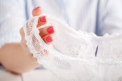 transparent panties on white background in female hands stock image