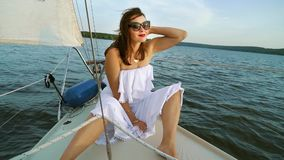 Sexy traveler in white dress enjoying voyage on sailboat. Sexy young woman in white dress and sun glasses sitting on bow of small sailboat. Attractive traveler stock video footage