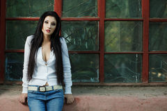 Sexy trendy brunette woman. Sexy fashionable brunette woman in trendy casual jeans and top showing her cleavage sitting on the windowsill  with copyspace Stock Photo