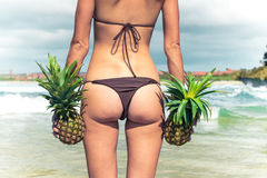 Sexy tropical woman butt close up with exotic pineapple fruit on the beach of paradise island of Bali. Healthy diet Stock Photos