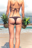 Sexy tropical woman butt close up with exotic pineapple fruit on the beach of paradise island of Bali. Healthy diet Royalty Free Stock Image