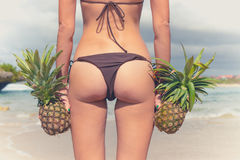 Sexy tropical woman butt close up with exotic pineapple fruit on the beach of paradise island of Bali. Healthy diet Stock Images