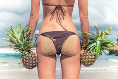 Sexy tropical woman butt close up with exotic pineapple fruit on the beach of paradise island of Bali. Healthy diet Royalty Free Stock Photos