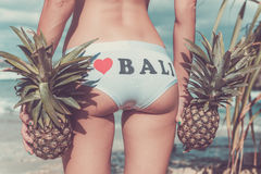 Sexy tropical woman butt close up with exotic pineapple fruit on the beach of paradise island of Bali. Healthy diet Stock Photography