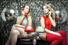 Sexy twins talking on phone Stock Images