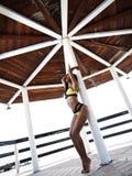 Sexy und anziehende Frau mit dünner gebräunter Zahl im Sportbikini wirft unter dem hölzernen Regenschirm auf dem Strand auf Lizenzfreie Stockfotos