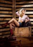 Sexy und glückliches Cowgirl, das in einer Scheune aufwirft Stockfoto