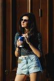 Sexy und hübscher Brunette in der Sonnenbrille mit Kaffee in der Hand Lizenzfreies Stockfoto