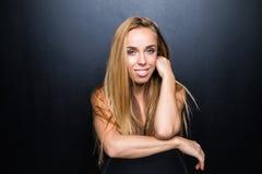 Sexy und schönes junges blondes Modell mit dünnem Körper wirft im Studio auf dem Stuhl, dunkle Wand auf dem Hintergrund auf Lizenzfreies Stockbild