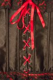 Underwear. Lace corset made of black silk. The scarlet ribbon is tied in a bow. Center cross lacing. Passion, playing in bed, seduction stock images