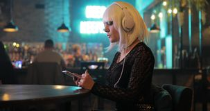 unusual girl in white wig listening to music with headphones in bar