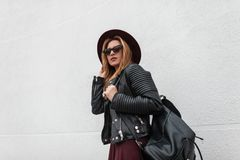 Sexy urban hipster young woman in a fashionable hat in stylish sunglasses in a vintage leather jacket with a backpack walks stock photography