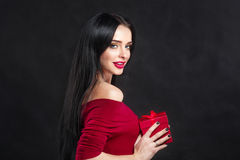 Sexy Valentine model Girl portrait. Gorgeous young brunette woman with red gift box. Perfect make up. Valentine` Day brunette lady Stock Photography