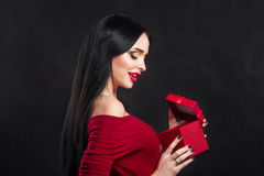 Sexy Valentine model Girl portrait. Gorgeous young brunette woman with red gift box. Perfect make up. Valentine` Day brunette lady Royalty Free Stock Photo
