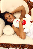 Sexy Valentine Woman. A beautiful black woman laying on a couch with a teddy bear. A great Valentines Day image Stock Photography
