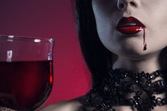 Sexy vampire girl with glass of wine or blood Royalty Free Stock Image