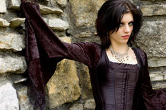 Sexy vampire woman. Sexy gothic emo vampire woman in black dress against old stone Stock Images
