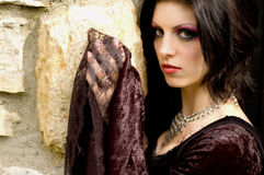 Vampire woman. Gothic emo vampire woman in black dress against old stone stock photography