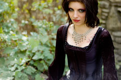 Sexy vampire woman. Sexy gothic emo vampire woman in black dress against old stone Stock Photos