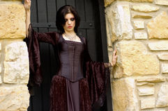Vampire woman. Gothic emo vampire woman in black dress against old stone stock photo