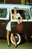 Vintage. Young Woman standing in alley next to old van stock photo
