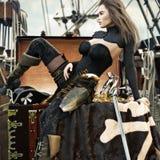 Sexy volwassen vrouwelijke piraat die met lang bruin haar van haar onlangs verworven schat aan boord van haar piraatschip geniete royalty-vrije illustratie