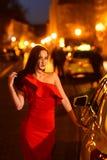 Sexy vrouw bij de auto Hollywoodster Modieus model van elegant meisje bij de straat van de nachtstad royalty-vrije stock afbeeldingen