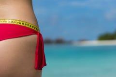 Sexy vrouw bij het strand in bikini met maatregelenband Het concept royalty-vrije stock fotografie