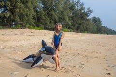 Sexy vrouw in blauw zwempak op het strand met opblaasbaar stuk speelgoed stock foto's