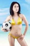 Sexy vrouw die bikini dragen die een voetbalbal houden Stock Foto's