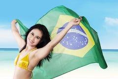 Sexy vrouw die Braziliaanse vlag op kust houden Royalty-vrije Stock Foto's